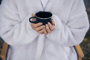 森でホーローカップを持ちイスに座り休憩する女性の写真素材 [FYI04681626]
