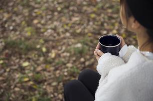 森でホーローカップを持ちイスに座り休憩する女性の写真素材 [FYI04681628]