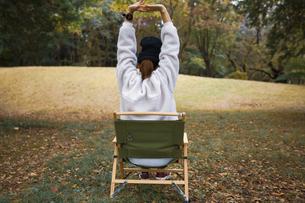 森にある椅子で伸びをする女性の後ろ姿の写真素材 [FYI04681629]