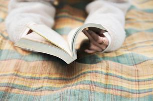 森の中でレジャーシートに寝転びながら本を読む女性の写真素材 [FYI04681630]