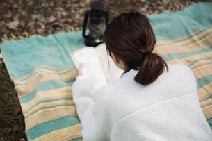 森の中でレジャーシートに寝転びながら本を読む女性の写真素材 [FYI04681631]