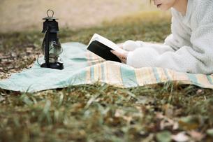 森の中でレジャーシートに寝転びながら本を読む女性の写真素材 [FYI04681634]