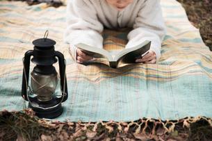 森の中でレジャーシートに寝転びながら本を読む女性の写真素材 [FYI04681636]