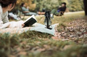 森の中でレジャーシートに寝転びながら本を読む女性の写真素材 [FYI04681647]