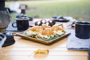木製テーブルの上に並べられたクロワッサンサンドのテーブル写真の写真素材 [FYI04681659]