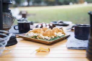 木製テーブルの上に並べられたクロワッサンサンドのテーブル写真の写真素材 [FYI04681660]