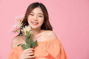 花を持っているきれいな若い女性の写真素材 [FYI04681973]