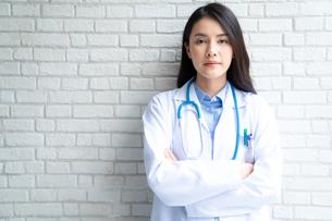 白い壁の前に立つ若い女性医師の写真素材 [FYI04682014]