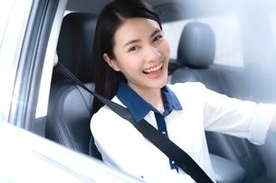 笑顔で車を運転している若い女性の写真素材 [FYI04682016]