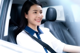 笑顔で車を運転している若い女性の写真素材 [FYI04682017]