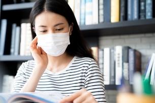フェイスマスクをつけて図書館で勉強している女子大生の写真素材 [FYI04682020]