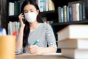 フェイスマスクをつけて図書館で携帯をかけながらメモを取る若い女性の写真素材 [FYI04682021]