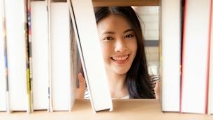 図書館の本棚で本を探している綺麗な女性の写真素材 [FYI04682022]