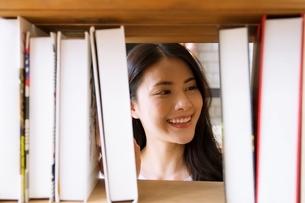 図書館の本棚で本を探している綺麗な女性の写真素材 [FYI04682025]