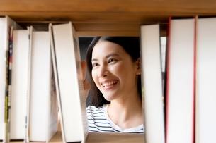 図書館の本棚で本を探している綺麗な女性の写真素材 [FYI04682026]