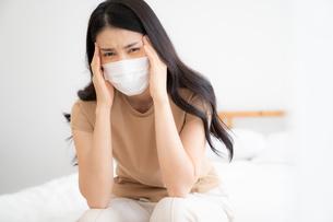 病気でマスクをつけて辛そうな表情している女性の写真素材 [FYI04682029]