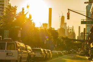 ニューヨーク市 ロングアイランドシティー クイーンズボロープラザの街並みの後ろに見えるマンハッタンの高層マンションの間に沈む夕日。の写真素材 [FYI04682056]