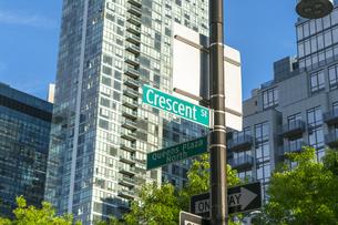 ニューヨーク市 ロングアイランドシティー クイーンズボロープラザの高層ビル群と新緑と道路標識。の写真素材 [FYI04682065]