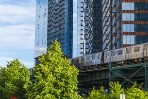 ニューヨーク市 ロングアイランドシティー クイーンズボロープラザの高層ビル群の間を走るニューヨーク市地下鉄。の写真素材 [FYI04682068]
