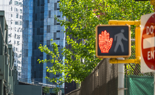 ニューヨーク市 ロングアイランドシティー クイーンズボロープラザの地下鉄高架線沿いの高層ビル群と新緑と歩行者信号。の写真素材 [FYI04682089]