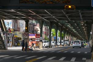 ニューヨーク市 ロングアイランドシティーの地下鉄高架線下を走る道路と商店街。の写真素材 [FYI04682114]