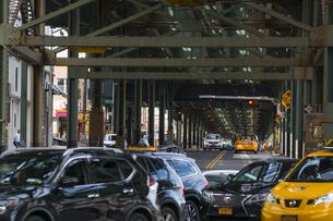 ニューヨーク市 ロングアイランドシティーの地下鉄高架線下を走る道路と車。の写真素材 [FYI04682117]