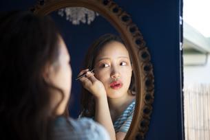 鏡を見ながらアイメイクをしている女性の写真素材 [FYI04682162]