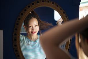 鏡を見ながら髪を結んでいる女性の写真素材 [FYI04682163]