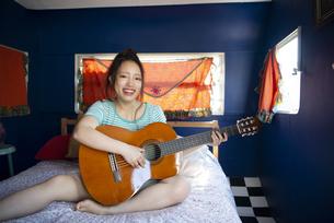 ベッドの上でギターを持っている女性の写真素材 [FYI04682172]