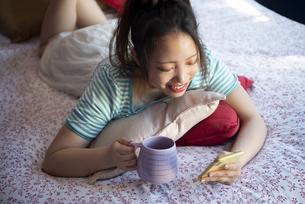 ベッドの上でスマホを触っている女性の写真素材 [FYI04682179]