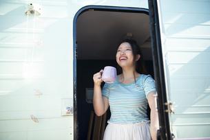 キャンピングトレーラーのドアを開けて笑っている女性の写真素材 [FYI04682201]