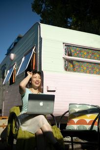 キャンピングトレーラーの前でパソコンを操作している女性の写真素材 [FYI04682204]