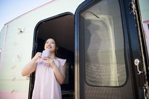 キャンピングトレーラーのドアを開けて笑っている女性の写真素材 [FYI04682215]