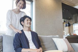 夫の肩を揉む妻の写真素材 [FYI04682286]