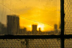 ひび割れたガラス越しニューヨーク マンハッタン  イーストビレッジの街並みを赤く染めながら沈む夕日。の写真素材 [FYI04682587]