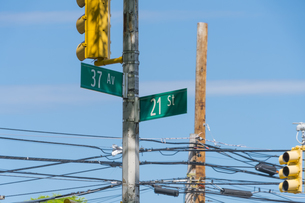 ニューヨーク市 ロングアイランドシティーに立つ交通信号機と道路標識。の写真素材 [FYI04682592]