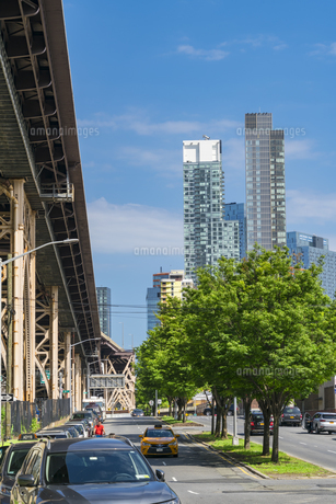 クイーンズ ボローブリッジ橋脚横の新緑越しにそびえ立つニューヨーク市 クイーンズ ロングアイランドシティー クイーンズボロープラザの新興高層ビル群。の写真素材 [FYI04682605]