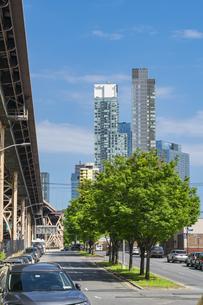 クイーンズ ボローブリッジ橋脚横の新緑越しにそびえ立つニューヨーク市 クイーンズ ロングアイランドシティー クイーンズボロープラザの新興高層ビル群。の写真素材 [FYI04682606]