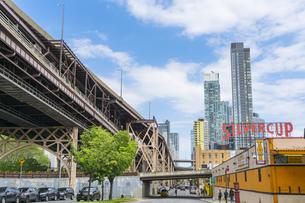 クイーンズ ボローブリッジ橋脚横の新緑越しにそびえ立つニューヨーク市 クイーンズ ロングアイランドシティー クイーンズボロープラザの新興高層ビル群。の写真素材 [FYI04682608]