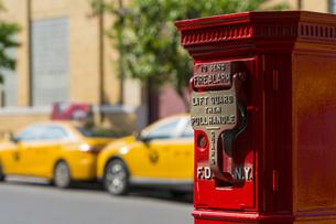ニューヨーク市 クイーンズ ロングアイランドシティー クイーンズボロープラザの火災報知機とイエローキャブ。の写真素材 [FYI04682615]