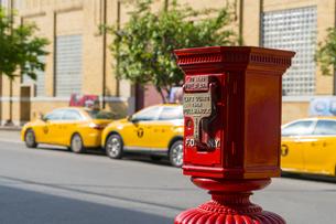 ニューヨーク市 クイーンズ ロングアイランドシティー クイーンズボロープラザの火災報知機とイエローキャブ。の写真素材 [FYI04682617]