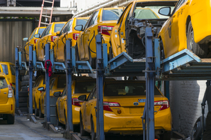 ニューヨーク市 クイーンズ ロングアイランドシティー クイーンズボロープラザの車修理屋に積まれたイエローキャブ。の写真素材 [FYI04682619]