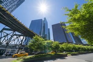 ニューヨーク市 ロングアイランドシティー クイーンズボロープラザの 新緑の並木道沿い高層ビル群の間を走るニューヨーク市地下鉄。の写真素材 [FYI04682633]