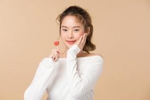 ハートの形をしているキャンディーを持つ可愛い女性の写真素材 [FYI04682929]