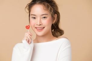 ハートの形をしているキャンディーを持つ可愛い女性の写真素材 [FYI04682930]