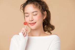ハートの形をするキャンディーを持つ綺麗な女性の写真素材 [FYI04682931]