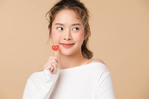 ハートの形をしているキャンディーを持つ可愛い女性の写真素材 [FYI04682932]