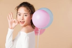 カラフルな風船を持って手でOKのサインをする可愛い女性モデルの写真素材 [FYI04682933]