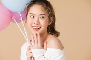 カラフルな風船を持っている可愛い女性モデルの写真素材 [FYI04682934]
