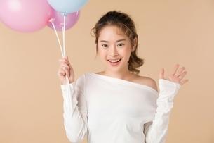 カラフルな風船を持っている可愛い女性モデルの写真素材 [FYI04682935]